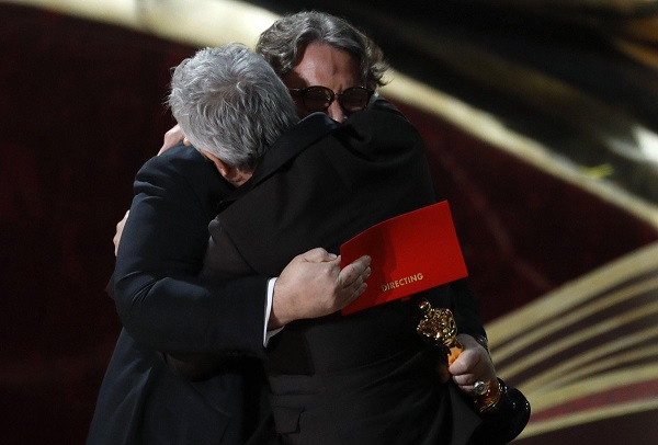 El Mejor Director sigue siendo mexicano. Del Toro le pasa la estatuilla al también director mexicano, Alfonso Cuarón | Foto: Twitter.