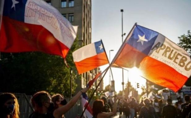 """Banderas de Chile con la leyenda """"APRUEBO nueva Constitución""""  Foto: publicada por Política Argentina."""